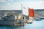 stock photo of maltese-cross  - the maltese flag is flying from upper Barrakka gardens in Valletta and on the background the fortifications of Cottonera - JPG