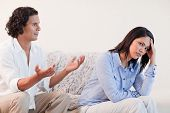 stock photo of apologize  - Young man on the sofa trying to apologize to his girlfriend - JPG