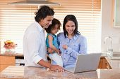 Young family using laptop in the kitchen together