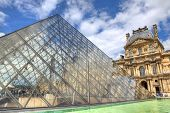 PARIS - JUNE 06: Glass Pyramid and Louvre (former Royal Palace) on background on June 06, 2012 in Pa