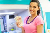 image of automatic teller machine  - happy young woman withdrawing or depositing cash at an ATM - JPG