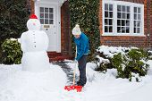 stock photo of snow shovel  - Woman shovels snow outside her home in UK - JPG