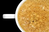 closeup of a cup with caffe latte on a black background