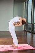 Full length of a young woman practicing yoga and making backbend at gym