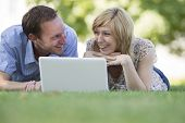 Couple lying on grass with laptop in park