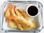 A fast-food carry-out of prawn tempura, known as shrimp tempura in the US, in an aluminium tray with a a pot of soy sauce.
