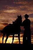 Cowboy Holding Horse In Sunset