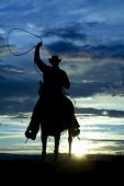 stock photo of western saddle  - A cowboy is riding forward in the sunset with a rope above his head - JPG
