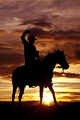 stock photo of reining  - A cowboy is sitting on his horse in the sunset and swinging a rope - JPG