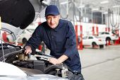 stock photo of greased  - Car mechanic working in auto repair service - JPG