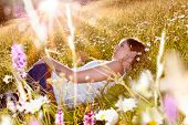 girl dreaming in a meadow full with flowers in the sunset