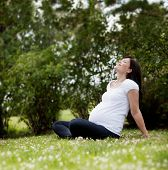 Happy attractive pregnant woman in park leaning back enjoying the sun