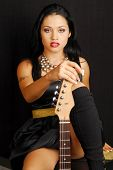 image of groupies  - Sultry hispanic female rocker holding her guitar - JPG