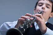 stock photo of clarinet  - Little enthusiastic artist playing on the clarinet