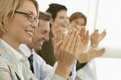 picture of spectacles  - Happy businesswoman with colleagues applauding at conference table - JPG
