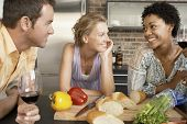 Smiling multiethnic friends preparing food at kitchen counter