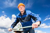 Senior Caucasian Worker In A Hardhat At The Factory With The Pipe Valve Against Blue Sky