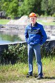 Senior Caucasian Manual Worker Standing Against Water Treatment Plant. Full-length