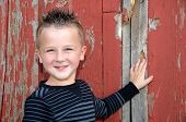 smiling young boy by barn