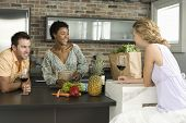 Cheerful multiethnic friends enjoying drinks at kitchen counter