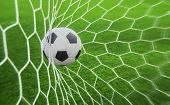 stock photo of shoot out  - soccer ball in goal with green background