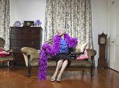 Feliz mujer senior con boa de plumas, sentado en el sofá en la sala de estar
