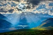 HImalayan valley landscape with Himalayas mountains. Sun rays come through clouds. Himachal Pradesh,