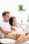 Couple relaxing together in sofa with laptop pc computer having fun. Romantic young happy multiracia