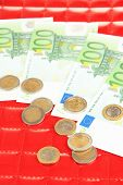 Euro banknotes and euro cents on red background