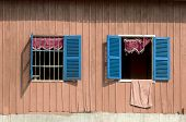 pic of kolam  - Facade of a wooden dwelling house with two open windows in Pre Kolam - JPG