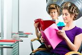 women at the hairdresser reading a magazine or a rag and chit-chat, while your hair drying under a h