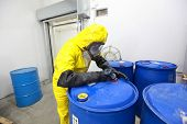 stock photo of rubber mask  - Professional in uniform filling barrels with chemicals - JPG