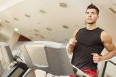 stock photo of treadmill  - Young man on a treadmill training at the gym - JPG