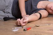 stock photo of overdose  - syringe with drugs and stoned addict lying on the floor - JPG