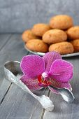 Sugar Tongs And Orchid Flower With Almond Cookies On Wooden Background