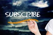 Businesswoman writing the word subscribe against stormy sky with tornado over landscape