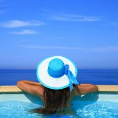 Woman overlooking the sea from swimming pool