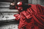 stock photo of murders  - Lying and bleeding woman in a red Victorian dress - JPG