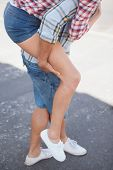 Man giving his girlfriend a piggy back on a sunny day in the city