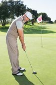 Golfer on the putting green at the eighteenth hole smiling at camera on a sunny day at the golf cour