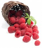 Raspberries With Leaves In A Basket Is Scattered