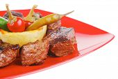 european food: grilled beef meat on red china plate isolated on white background with capers and bbq