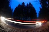 Cars going fast through a curve on a forest road at dusk, on a rainy day - i.e. Potentially dangerou