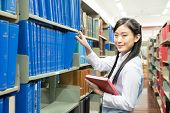 Asian Girl Student Picking A Book In A Library