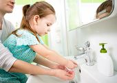 pic of water jet  - kid girl washing hands with mom help - JPG