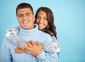 Portrait of amorous couple in fashionable pullovers looking at camera with smiles