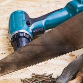 picture of joinery  - Battery-operated portable hand drill with timber screwdrivers and screws surrounded by fresh wood shavings in a carpentry joinery DIY or construction concept