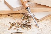 image of joinery  - Close up view of a Phillips head screwdriver and threaded metal wood screws with one screw inserted into a plank of wood in a carpentry joinery and construction concept - JPG