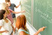 Math lesson student write on green chalkboard with classmates pointing
