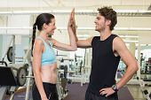 Fit man and woman high fiving at the gym
